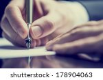 Stock photo retro effect faded and toned image of a man writing a note with a fountain pen 178904063