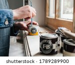 Small photo of Paris, France - May 30, 2020: Close-up side view of woman mixing paint sample pot of Farrow and ball luxury British paint preparing to paint the wall and window frame