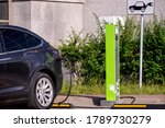 Modern electric car on charging spot in front of office buildings - stock photo