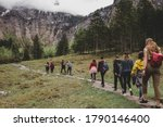 Group of tourists hike to Rothbach waterfall throw pine forest on background of rock mountains & cloud sky. Bavaria. Germany