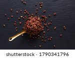 Food spices concept top view of organic Sichuan, Szechuan pepper in copper cup on black slate stone with copy space