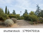Outdoor stairs of a park full of different vegetation and a vintage streetlamp on a blue sky with clouds.
