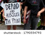 """Small photo of Washington, DC, USA - August 1, 2020: Two young women brought signs to the Demand DC rally and march, one of which says, """"Defund and Abolish the Police"""""""