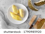 Small photo of Topview of ripe durian, wood cutting board with knife and durian rind on table.