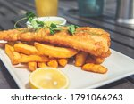 Small photo of Traditional English Food such as Fish and Chips with green mushy peas served in the Pub or Restaurant