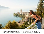 Young beautiful woman tourist admiring amazing view of Montreux city, Switzerland, canton of Vaud