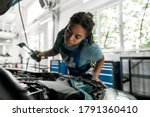 Young african american woman, professional female mechanic examining under hood of car with torch at auto repair shop. Car service, maintenance and people concept. Selective focus. Horizontal shot - stock photo