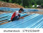 Constructor worker using a measuring tape to measure the dimension of roof steel structure work. - stock photo