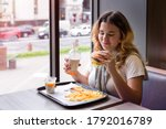 Asian Young Girl Sits At Table...