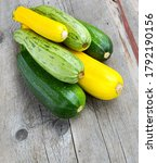 Small photo of Zucchini on wooden background. Yellow and green zucchini. Vegetable marrow courgette or zucchini. Harvest courgette organic ingredient.