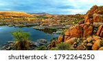 Small photo of Sunset after late summer storm at Lake Watson, Prescott, Arizona with golden rocks over still blue skies with sky reflection