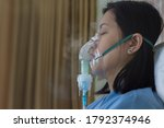 Small photo of Sickness female in blue clothe wearing nasal mask with respiratory problem in hospital room. Asian woman patient inhalation therapy by the mask of inhaler with soft stream smoke from bronchodilator.