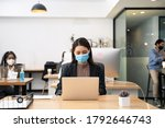 Small photo of Asian young businesswoman working on computer in office with new normal lifestyle concept. Man and woman wear protective face mask and keep distancing to prevent covid virus after company reopen again