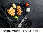 Small photo of Fish and chips. Traditional british hot dish fried fish, potato chips, mushy minty peas and tartare sauce and ketchup view from above, black stone background space for text