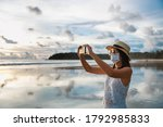 Small photo of New normal travel concept, Happy traveler asian woman with mask and mobile phone sightseeing in Kata beach, Phuket, Thailand