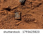 Small photo of A hiking shoe footprint in a brown desert sand with a part of it on some square rock that looks misplaced.