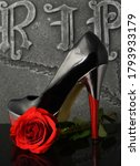 Small photo of A womans shoe and red rose overtop of a gravestone to show respect for a lost loved one.