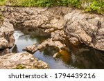 Small photo of Strange rock formation due to the physical abrasion and scouring of a river, by rocks and water in a gorge on the Water of Ken river, exposed due to the dewatering of Earlstoun Dam, Scotland
