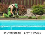 New Grass Turfs Installation Along Side of Garden Outdoor Swimming Pool. Caucasian Gardener in His 40s Assembly Grass From Rolls. Landscaping Industry. - stock photo