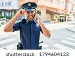 Small photo of Young handsome hispanic policeman wearing police uniform smiling happy. Standing with smile on face having conversation talking on the smartphone at town street.