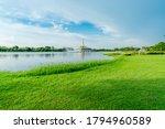 Lake And Green Grass Field At...