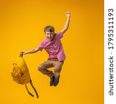 Small photo of cheerful mischievous schoolboy in uniform with a backpack jumps on a yellow background. Dynamic images that go back to the school concept. beginning of holidays. Back to school. boy is ready to study.