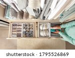 Small photo of Unidentified neat housewife puts container with socks and pantyhose on wardrobe drawer during general cleaning by modern storage system. Concept of beautiful and comfortable organization