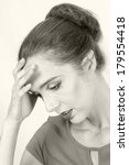 A monochrome portrait of a young woman suffering a headache , stress or pain  - stock photo