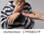 Small photo of female hand holds out, offering, a handful of colored pills and capsules, boy, a child in a striped jumper holds on to the lower jaw, the second hand hung limp from suffering, toothache concept