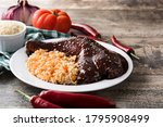 Small photo of Traditional mole Poblano with rice in plate on wooden table. Copy space