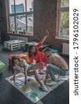 Small photo of Party activities. Three friends playing active twister game at the party
