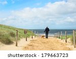 Stock photo coast from northsea at dutch wadden island texel with man and dog 179663723