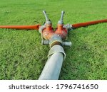 Small photo of Old red two way diverting water valve on green lawn.