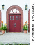 Two Tall Red Doors With Small...