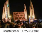 """Small photo of Bangkok Thailand-Aug16,2020: protester with face mask shows the sign """"LISTEN TO THE PEOPLE"""" at Democracy Monument-Thailand to against the government"""