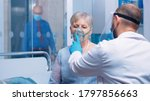 Small photo of Doctor in mask and visor helping old lady to breathe with a respiratory oxygen mask while sitting on hospital bed in modern private clinic. Coronavirus covid-19 outbreak healthcare crisis.