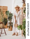 Small photo of Fashionable woman wearing summer white crochet jumpsuit, straw hat, sandals, holding wicker bag, posing at home, in stylish boho interior with green tropical plants. Full-length indoor portrait