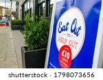 Small photo of London- August, 2020: Eat Out to Help Out sign on London high street- UK Government scheme to help restaurants through the Covid 19 downturn