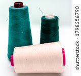 Small photo of Three bobbin threads isolated on white background. Close up of spools of green and pink shades of sewing thread. Thread is a type of yarn used for sewing.