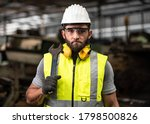 Portrait of technician man or industrial worker with hardhat or helmet, eye protection glasses, Tool and vest working electronic machinery on laptop and mechanical  in Factory of manufacturing place