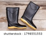 Small photo of Black rubber boot ( galoshes ) isolated on wooden table background. Top view. Flat lay.