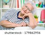 Smiling Senior Woman Sitting At ...