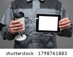CCTV installation worker with a security camera and blank screen digital tablet close up. - stock photo