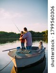 Young Family Fishing On Boat In ...