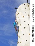 A Young Boy Is Climbing A...