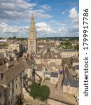 Aerial photography of the town centre of Stamford, Lincolnshire, UK. Showing a blue sky with clouds, pretty rooftops and many church spires.