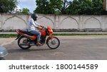 Small photo of Reengus, Jaipur, India- 20 April, 2020; A man wearing helmet rides motorbike along city street. People who wear helmet abide by traffic laws.