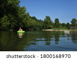 Woman gently floats the Caddo River, Glenwood, Arkansas. A women is in a lime green intertube and has just left the entrance beach that has other floatation devices ready for floaters.
