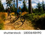 Small photo of Cycling woman and men riding on bikes on forest gravel road. Couple cycling MTB enduro flow trail track. Outdoor sport activity.