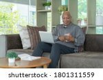 Small photo of Business senior old elderly Black American man, African person using a smartphone or mobile phone in living room at home in technology device concept. Lifestyle people.